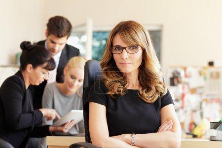Photo pour Exécutif femme souriant dans le bureau, avec ses collègues en arrière-plan - image libre de droit