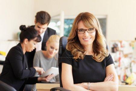 Photo pour Heureuse femme d'affaires avec des collègues en arrière-plan au bureau - image libre de droit