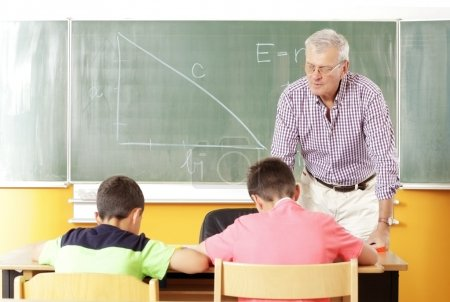 Photo for Elementary classroom setting. Focus on teacher and chalkboard. - Royalty Free Image
