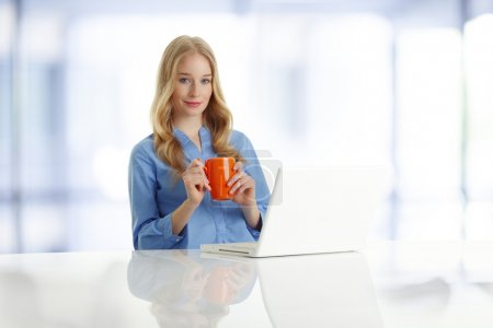 Photo for Portrait of beautiful young woman sitting at desk with laptop and mug. - Royalty Free Image