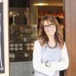 Beautiful small coffee shop owner standing in faca...