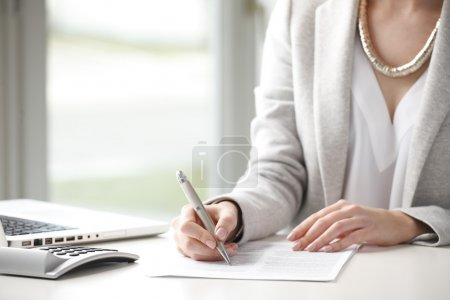 Photo pour Gros plan de femme d'affaires assis au bureau et remplissez le formulaire - image libre de droit