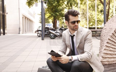 Photo for Modern young businessman sitting in front of business center, while working on digital tablet. - Royalty Free Image