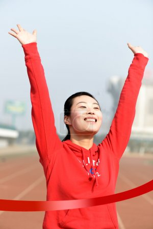 Conceptual image of an Asian Business woman winning a race