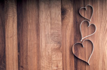Valentine's day paper hearts on wooden background.