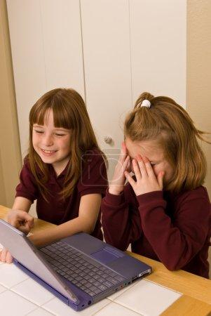 Photo pour Deux jeunes filles travaillant sur un ordinateur portable. une jeune fille couvre son visage dans l'embarras comme les autres sourires de la jeune fille et fait remarquer, ce qui semble être une erreur, sur l'écran. mise au point sélective minimal utilisé pour attirer l'attention sur la fille en arrière. - image libre de droit