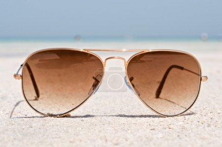 Photo pour Lunettes de soleil et réserver sur une plage de sable à Dubaï, EAU - image libre de droit