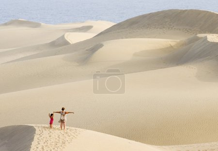 Woman and daughter walking in the dunes of Maspalomas