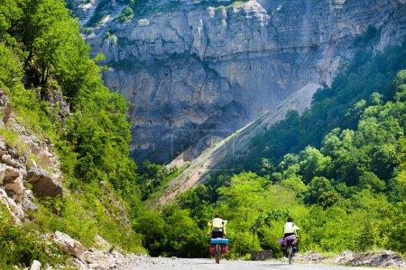 Photo pour Touristes en VTT sur une route de gravier en une journée - image libre de droit