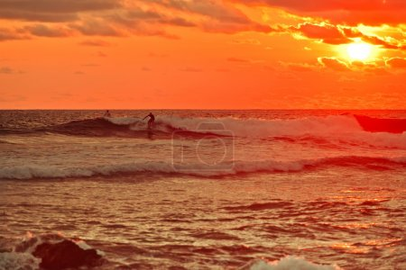 Photo for Silhouette. surfer standing on the crest of a wave board. Orange sky with clouds, sunset. - Royalty Free Image