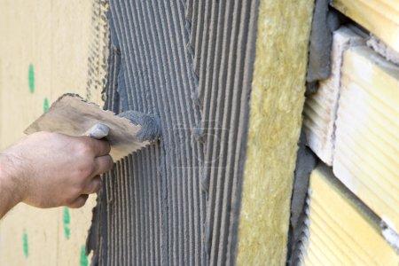 Foto de Aplicación de recubrimiento sobre aislamiento, pared de ladrillo, bateo - Imagen libre de derechos