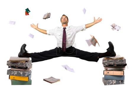 Photo pour Homme d'affaires faisant se divise sur la pile des dossiers avec des papiers tout autour - image libre de droit