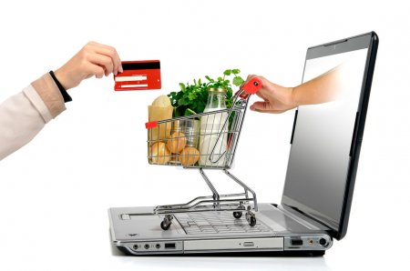 Photo for Hand with credit card and a small shopping cart coming from laptop screen isolated in white - Royalty Free Image