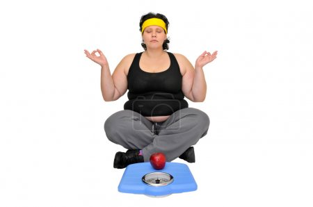 Photo for Large girl sitting near a scale with an apple doing yoga exercises - Royalty Free Image