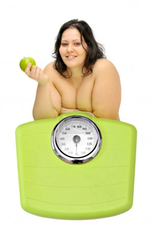 Photo for Beautiful nude large girl with an apple iand weight scale - Royalty Free Image