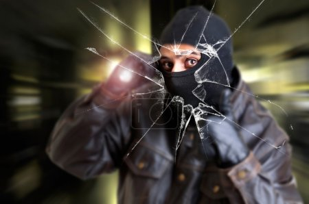 Photo for Burglar with flashlight over a broken glass - Royalty Free Image