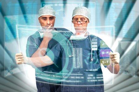 Photo pour Equipe de médecins en uniforme avec rayons X et écrans numériques - image libre de droit