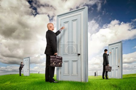 Photo for Businessmen or salesmen with briefcases knocking at several doors in a green field - Royalty Free Image