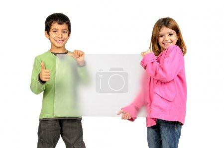 Photo pour Couple d'enfants posant avec un tableau blanc isolé en blanc - image libre de droit