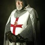 Knight Templar posing with sword in a dark backgro...