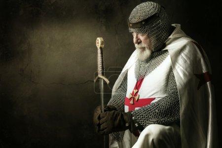 Templar knight praying in a dark background...