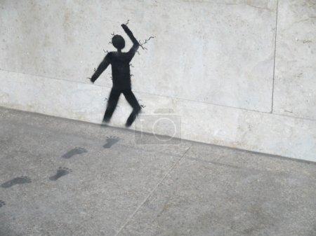 Artwork painting on grey stone, man running through stone wall