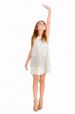 Photo for Little girl trying to be taller isolated in white - Royalty Free Image