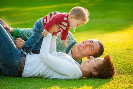 Photo pour Famille jouant sur l'herbe dans le parc - image libre de droit