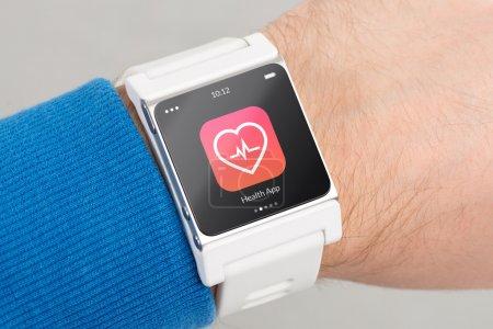 Photo pour Fermer montre intelligente blanche avec icône de l'application de santé sur l'écran est à portée de main - image libre de droit