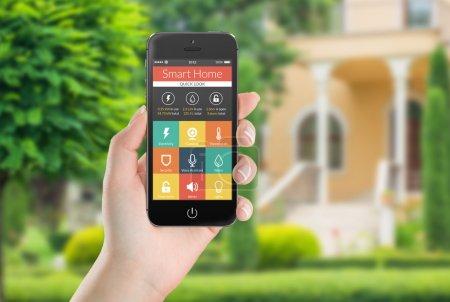 Photo pour Main féminine tenant noir Smartphone mobile avec une application maison intelligente sur l'écran. maison de flou sur le fond. pour accéder à toutes les commandes de votre maison et s'occuper de la sécurité à la maison. - image libre de droit