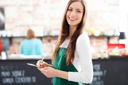 Young waitress holding notepad in cafe