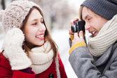 Mladý muž brát fotografie ženy v zimě