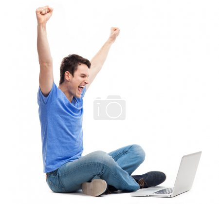 Excited young man using laptop