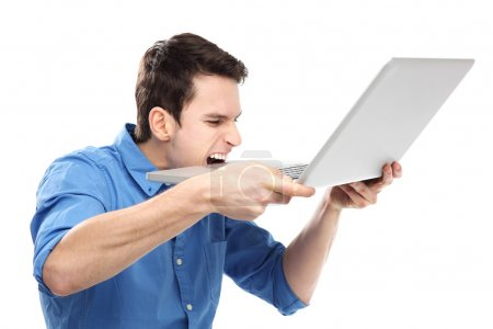 Photo for Man biting a laptop in frustration - Royalty Free Image