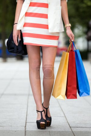 Legs and heels of woman with shopping bags