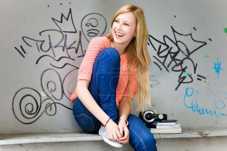 Photo for Young woman sitting in front of graffiti - Royalty Free Image