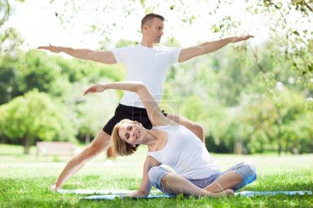Photo pour Couple pratique l'yoga dans le parc - image libre de droit
