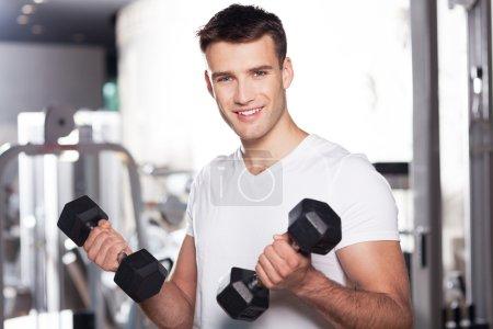Photo pour Jeune homme travaillant dans la salle de sport, soulevant des haltères - image libre de droit