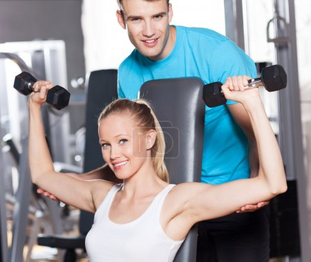 Photo for Trainer helps Woman Lifting Dumbbells - Royalty Free Image