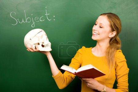 Photo pour Étudiante tenant crâne et livre - image libre de droit