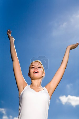 Woman with arms raised outdoors