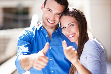 Smiling couple with thumbs up