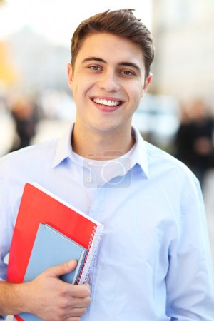 Photo for Male student with notebook smiling - Royalty Free Image