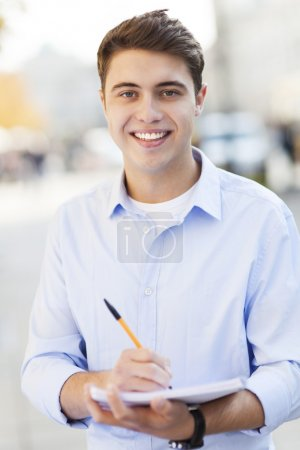 Photo for Male student with notebook and pen smiling - Royalty Free Image