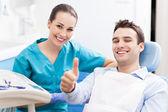 Mann Daumen bei Zahnarztpraxis aufgeben