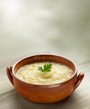Steaming bowl of potato soup on wooden table