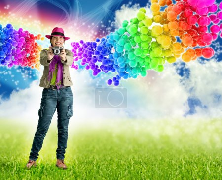 Smiling woman holding a camera in rainbow bubbles