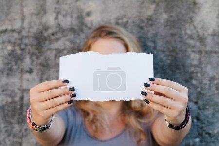 Photo pour Adolescente en vêtements décontractés tenant feuille blanche de papier - image libre de droit