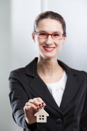 Photo pour Clé de maison donnant jeune femme d'affaires - image libre de droit