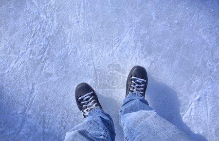 Photo pour Regardant vers le bas sur des patins à glace debout sur une patinoire - image libre de droit